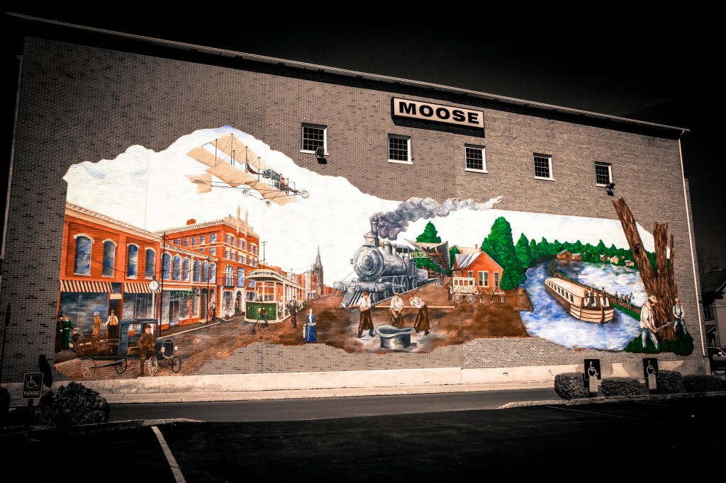 """This particular mural focuses on the transportation history of Milton. Depicted are the town's many means of transportation, from trucking, to the small dirt airport that used to exist, to the grand canal system. Also pictured are numerous inventions that have originated in Milton, including """"fly nets"""" for horses and tub cars which enabled trains to haul liquid. Milton remains a prominent transportation hub in Pennsylvania today, so this story remains relevant."""